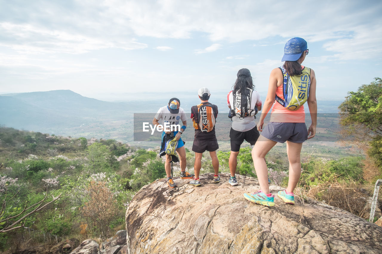 adventure, mountain, day, friendship, full length, leisure activity, rear view, togetherness, real people, standing, sky, lifestyles, outdoors, men, nature, women, group of people, scenics, sport, sports clothing, young women, young adult, beauty in nature, adult, people
