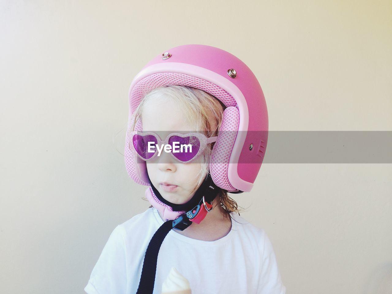 Close-up of cute girl wearing pink helmet