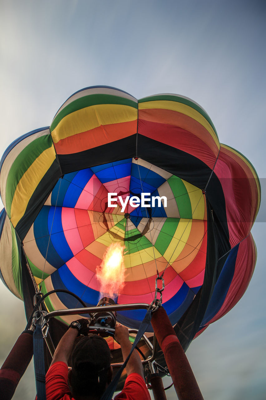 multi colored, sky, real people, nature, lifestyles, people, balloon, low angle view, hot air balloon, leisure activity, day, body part, transportation, sport, air vehicle, adventure, human body part, outdoors, men, holding