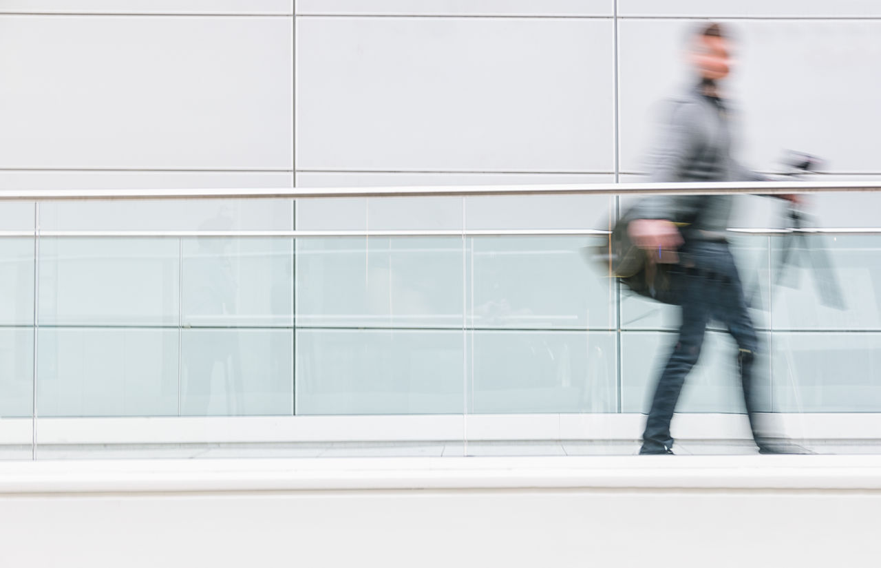 Blurred Motion Of Man Walking Against Building