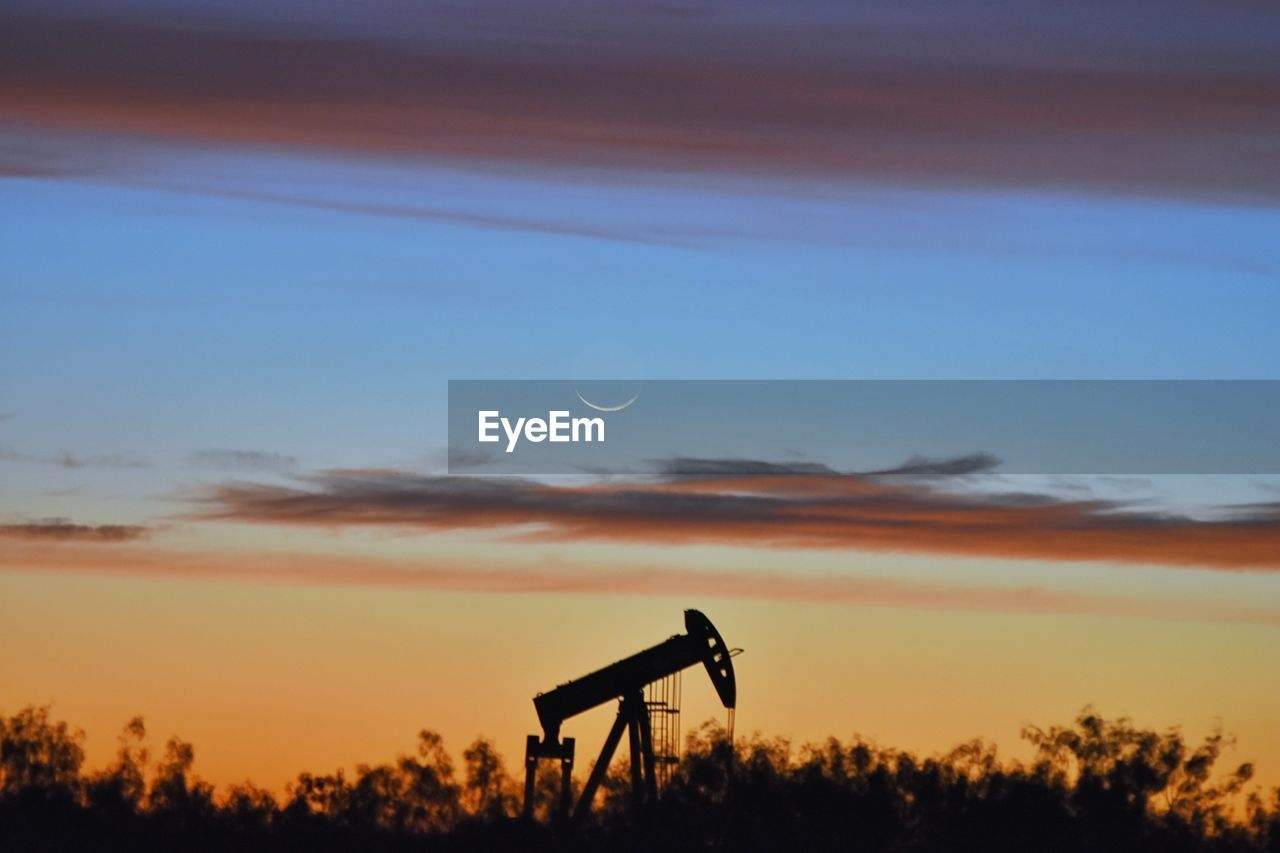 Silhouette oil pump amidst trees against orange sky during sunset