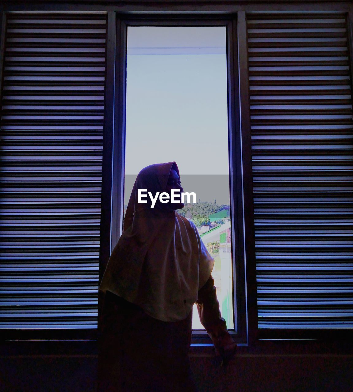 Young woman wearing hijab while standing by window at home