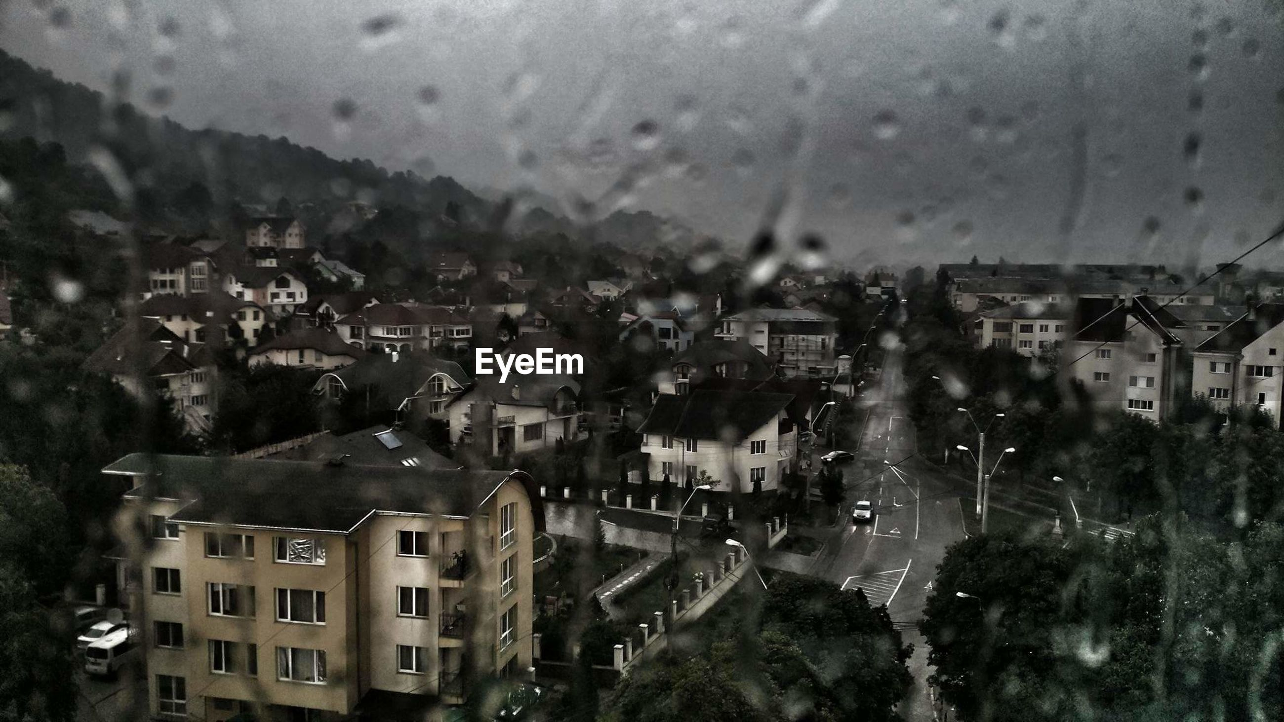 Cityscape against sky seen through window at home during rain