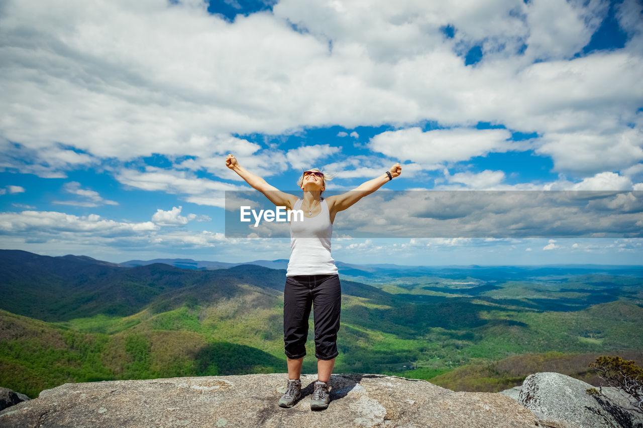 Full length of woman standing on rock against sky