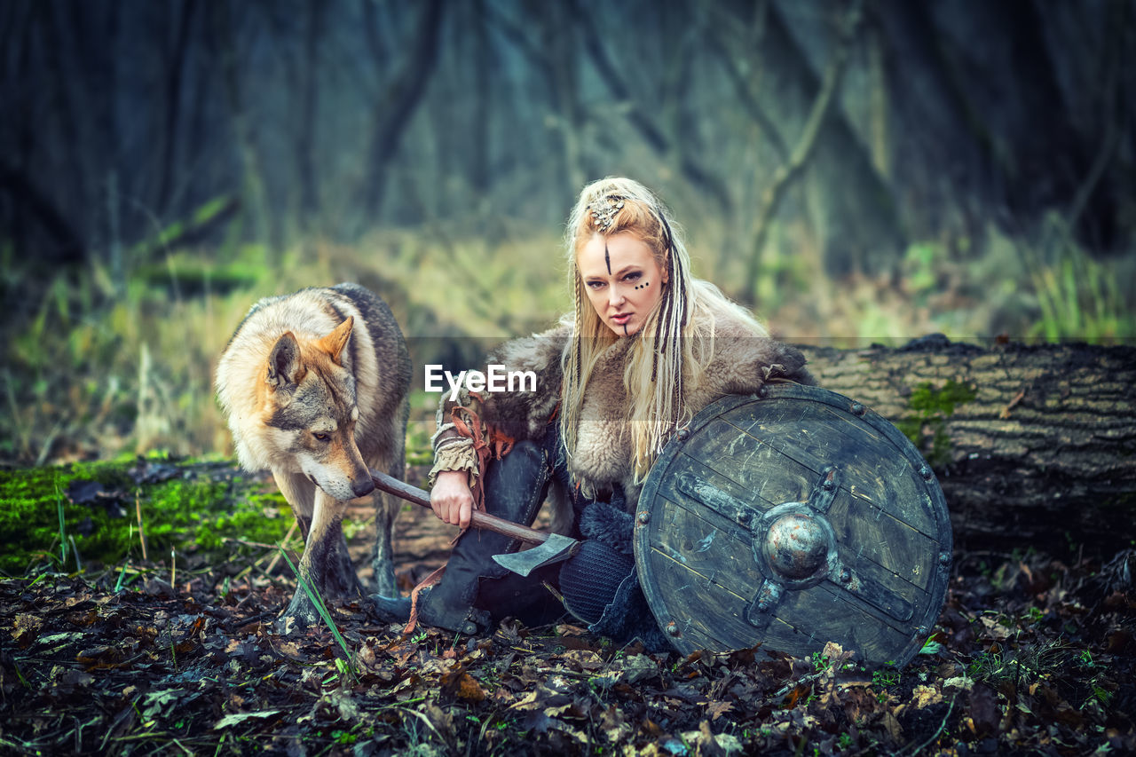 Portrait of young woman holding axe while sitting with wolf in forest
