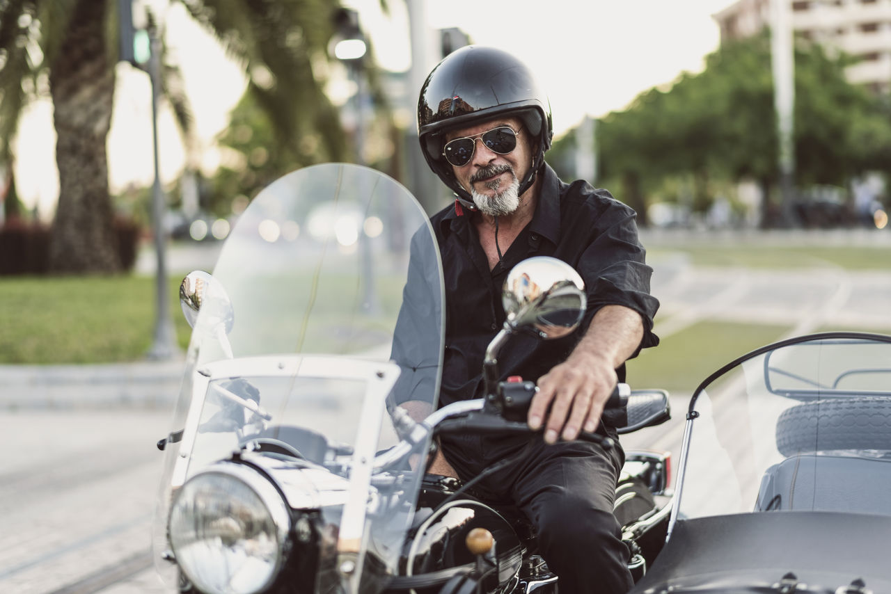 Portrait of mature man wearing sunglasses while riding motorcycle on road