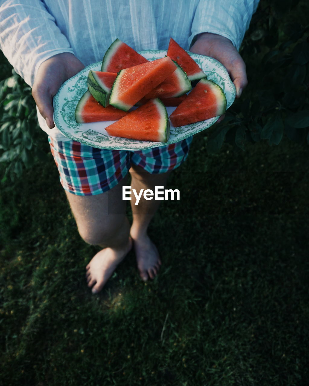 Low Section Of Woman Holding Watermelon In Plate
