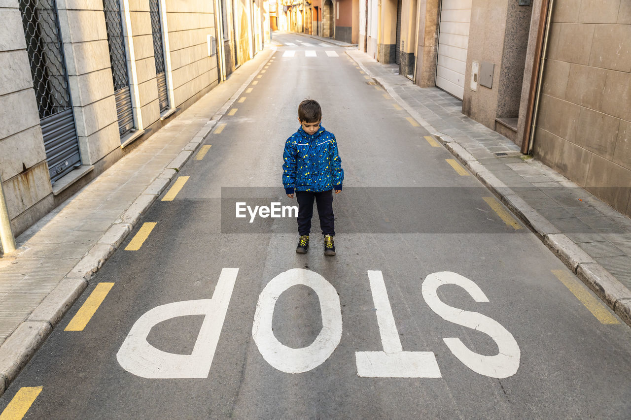 Boy Standing By Stop Text On Road