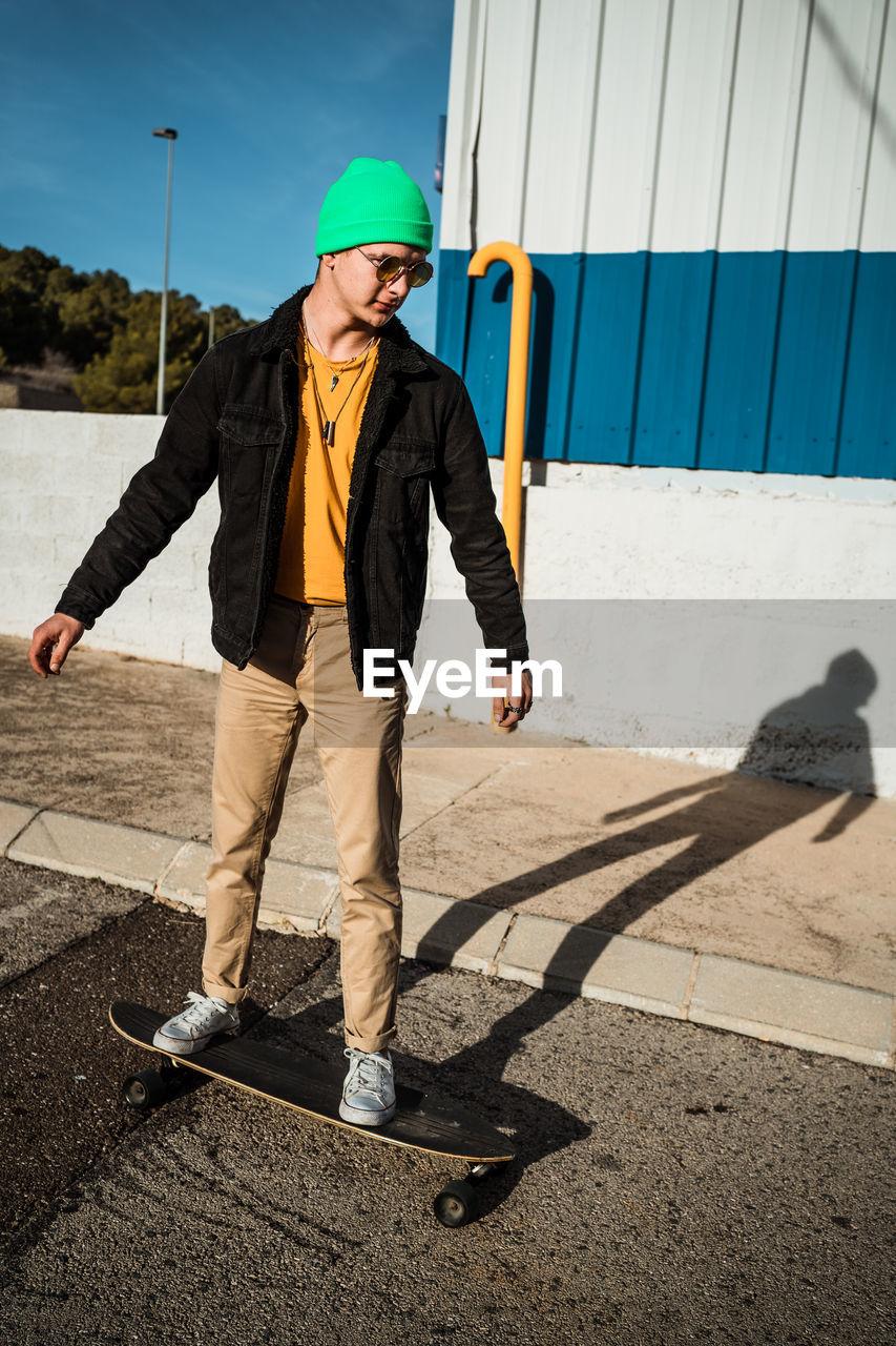 Full length of man standing on skateboard on street