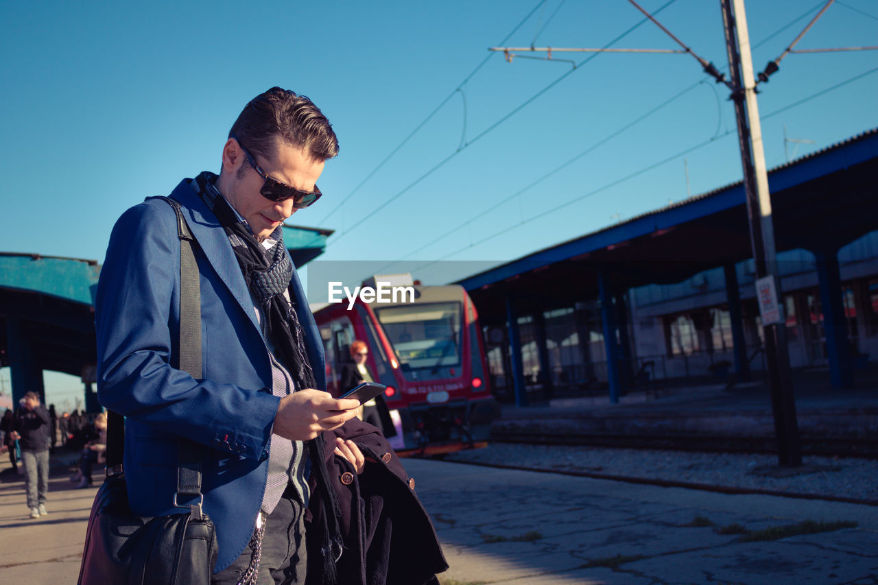Handsome Man Using Phone At Railroad Station Platform
