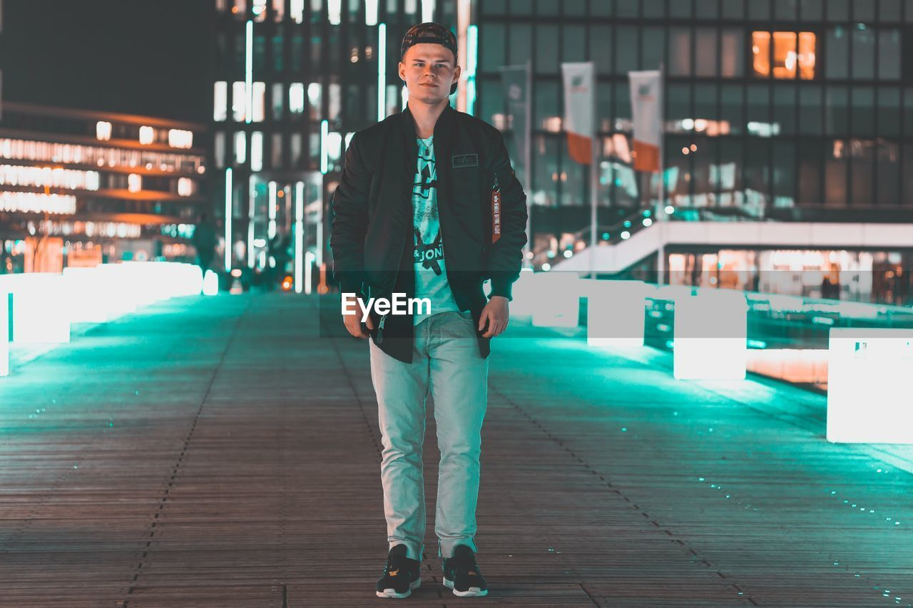 one person, full length, real people, looking at camera, front view, lifestyles, portrait, leisure activity, focus on foreground, young adult, casual clothing, happiness, outdoors, young men, standing, smiling, building exterior, night, city, winter, cold temperature, men, warm clothing, architecture, people