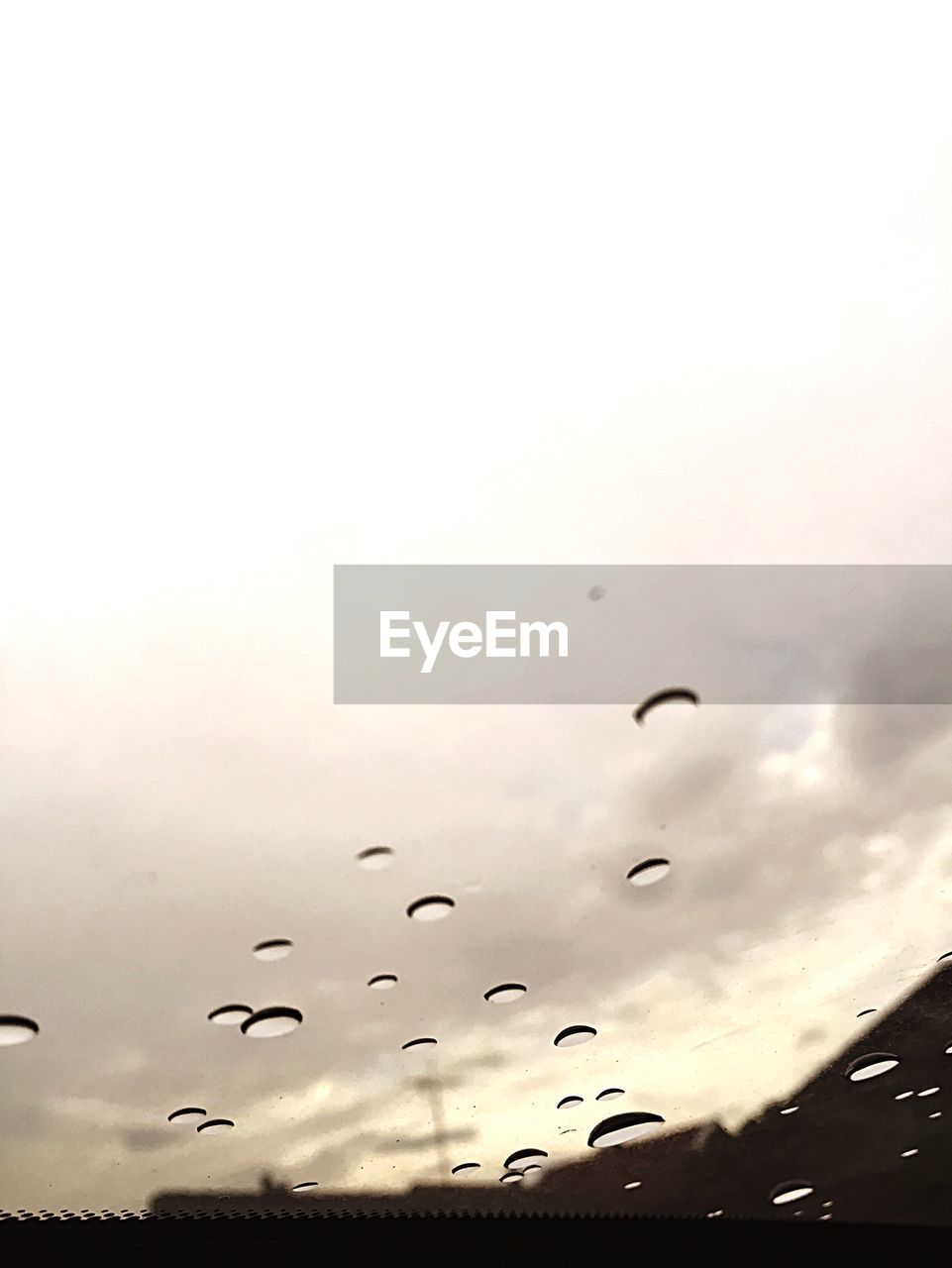 Low angle view of cloudy sky seen through wet windshield