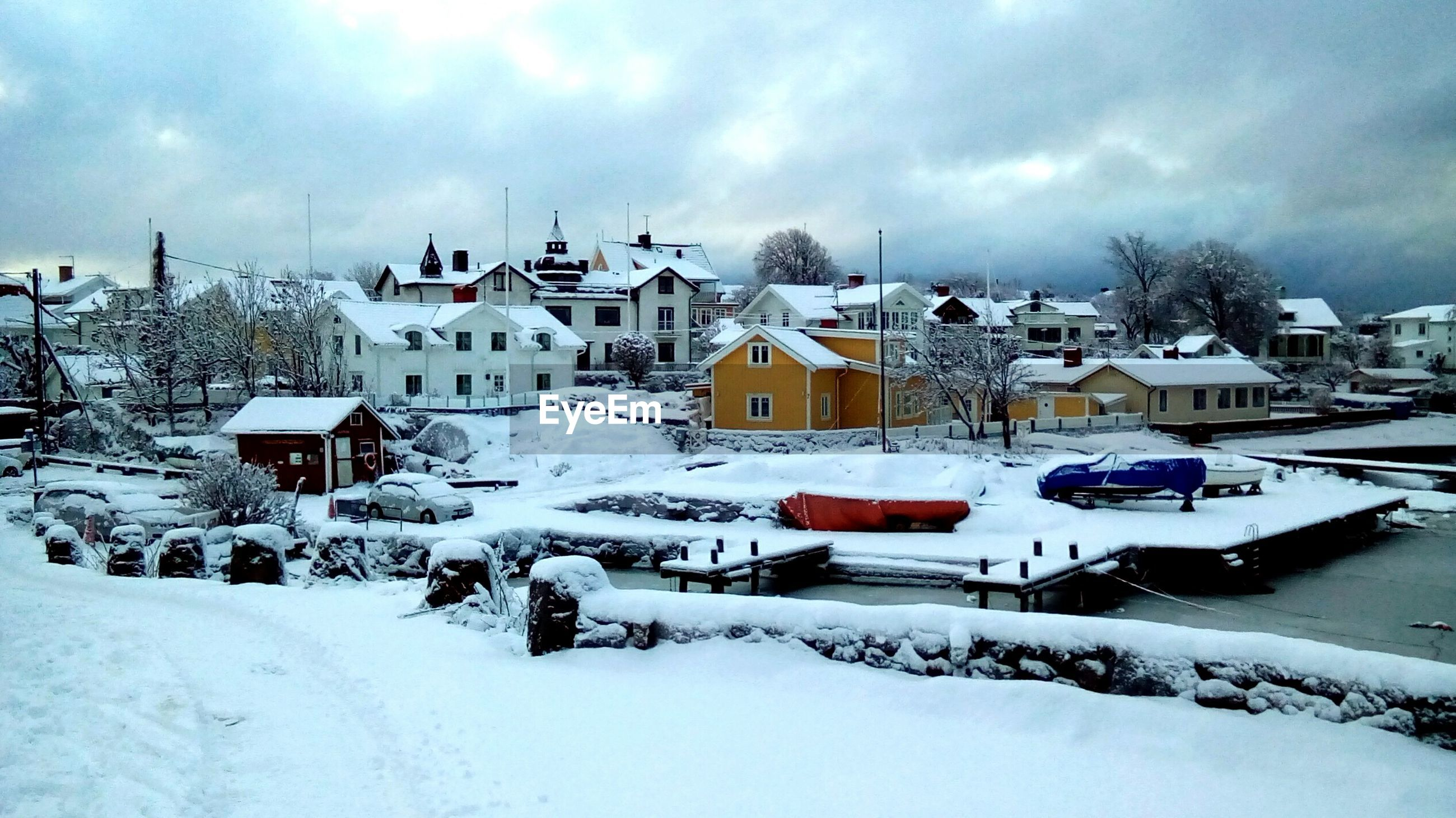 Cars parked on snow covered landscape against cloudy sky