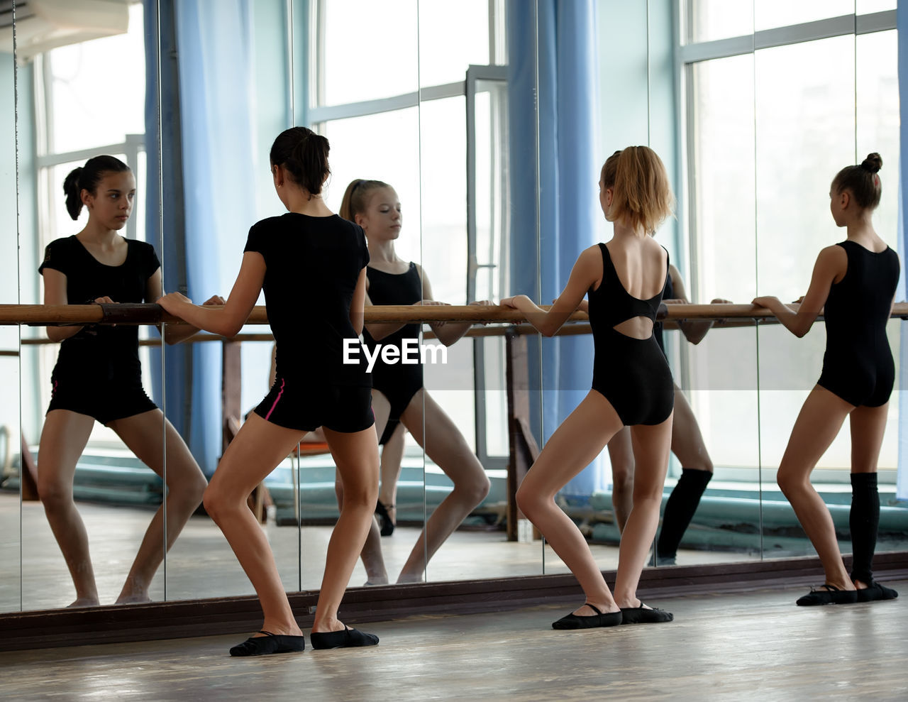 group of people, indoors, dancing, ballet, practicing, women, real people, young women, dance studio, lifestyles, ballet dancer, performance, young adult, people, togetherness, focus on foreground, exercising, girls, adult, skill, teenager