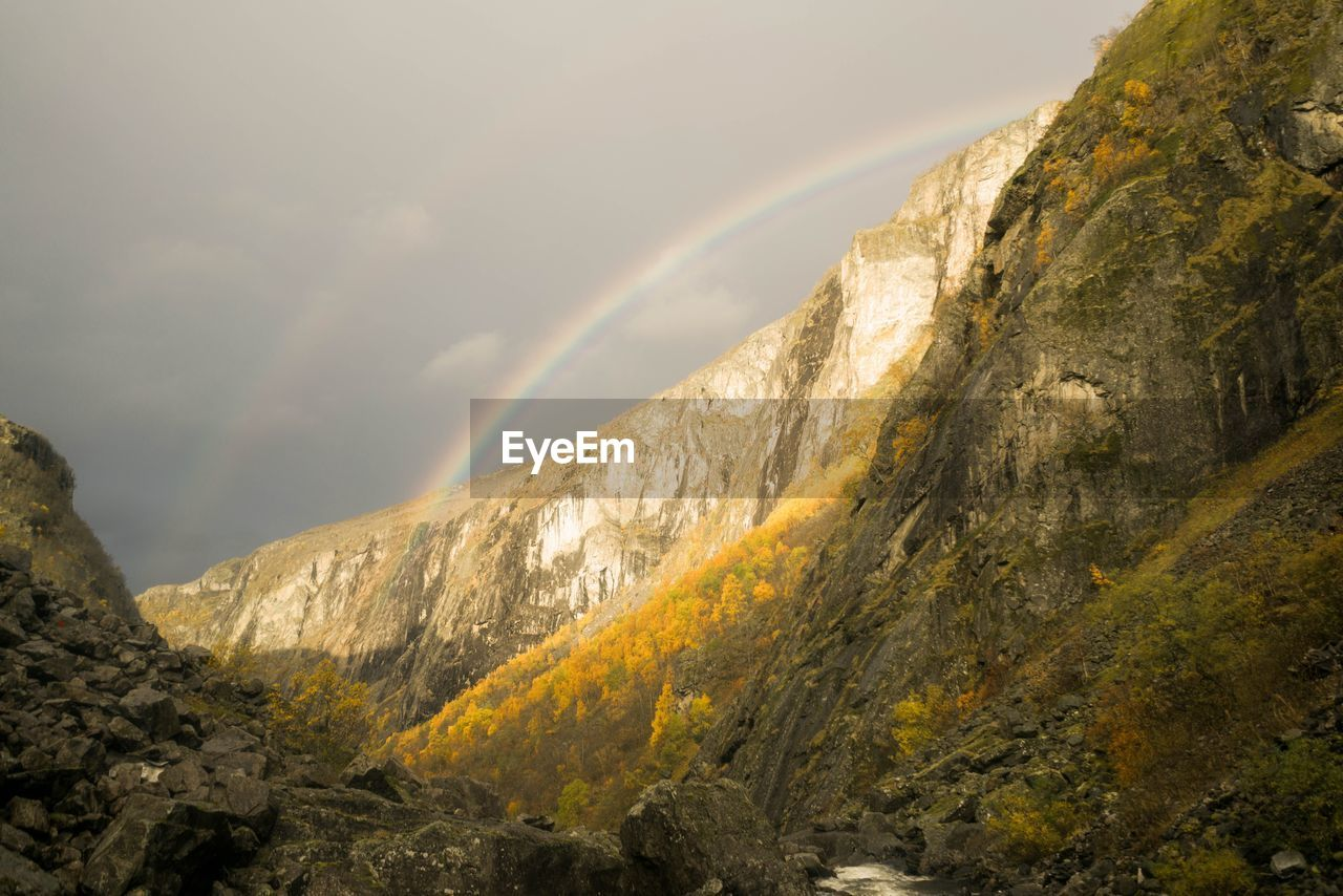 mountain, scenics - nature, beauty in nature, cloud - sky, sky, nature, rock, tranquil scene, tranquility, mountain range, non-urban scene, no people, day, rock - object, rainbow, solid, environment, remote, idyllic, formation, outdoors, mountain peak, eroded