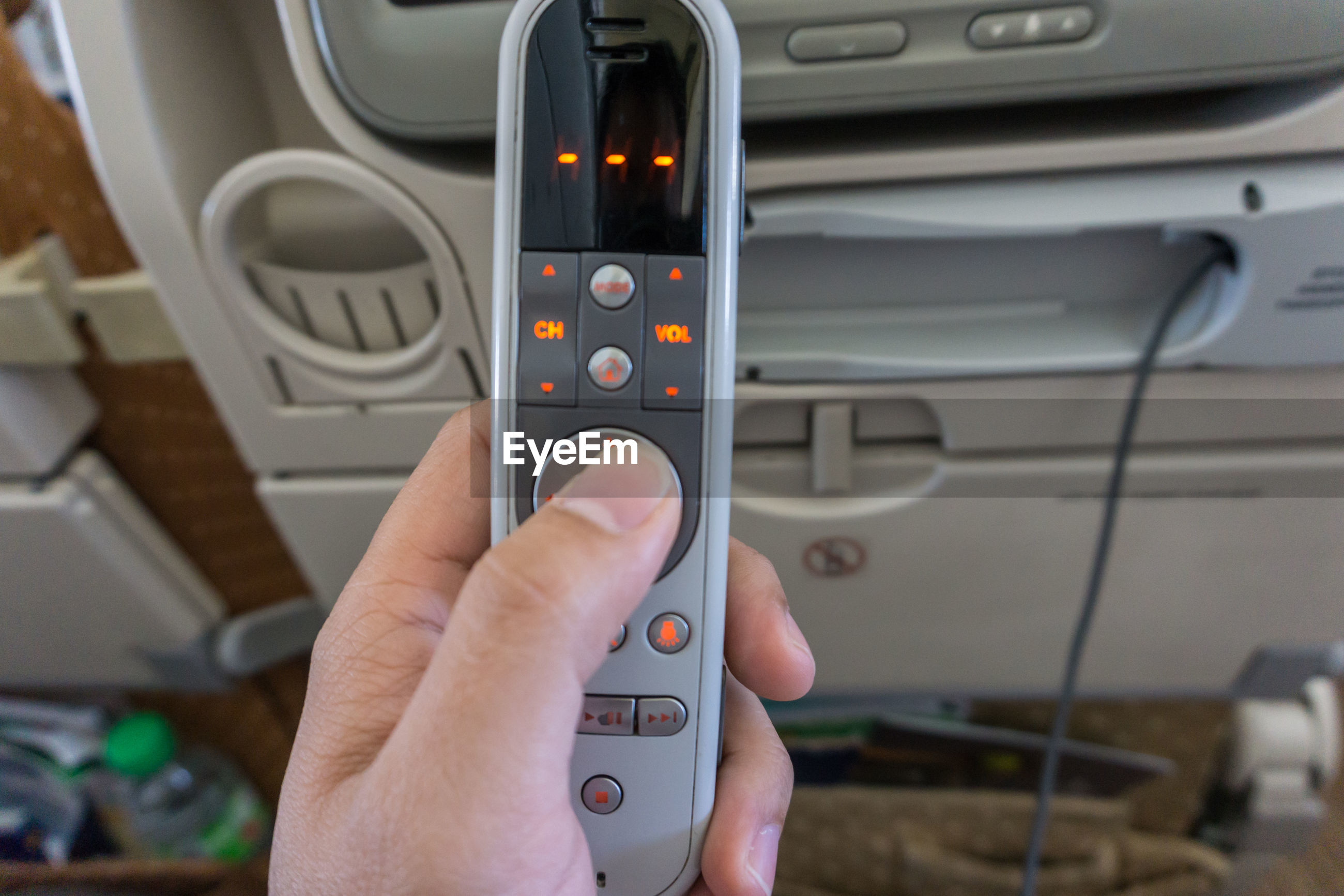 Cropped hand of person holding remote control in airplane