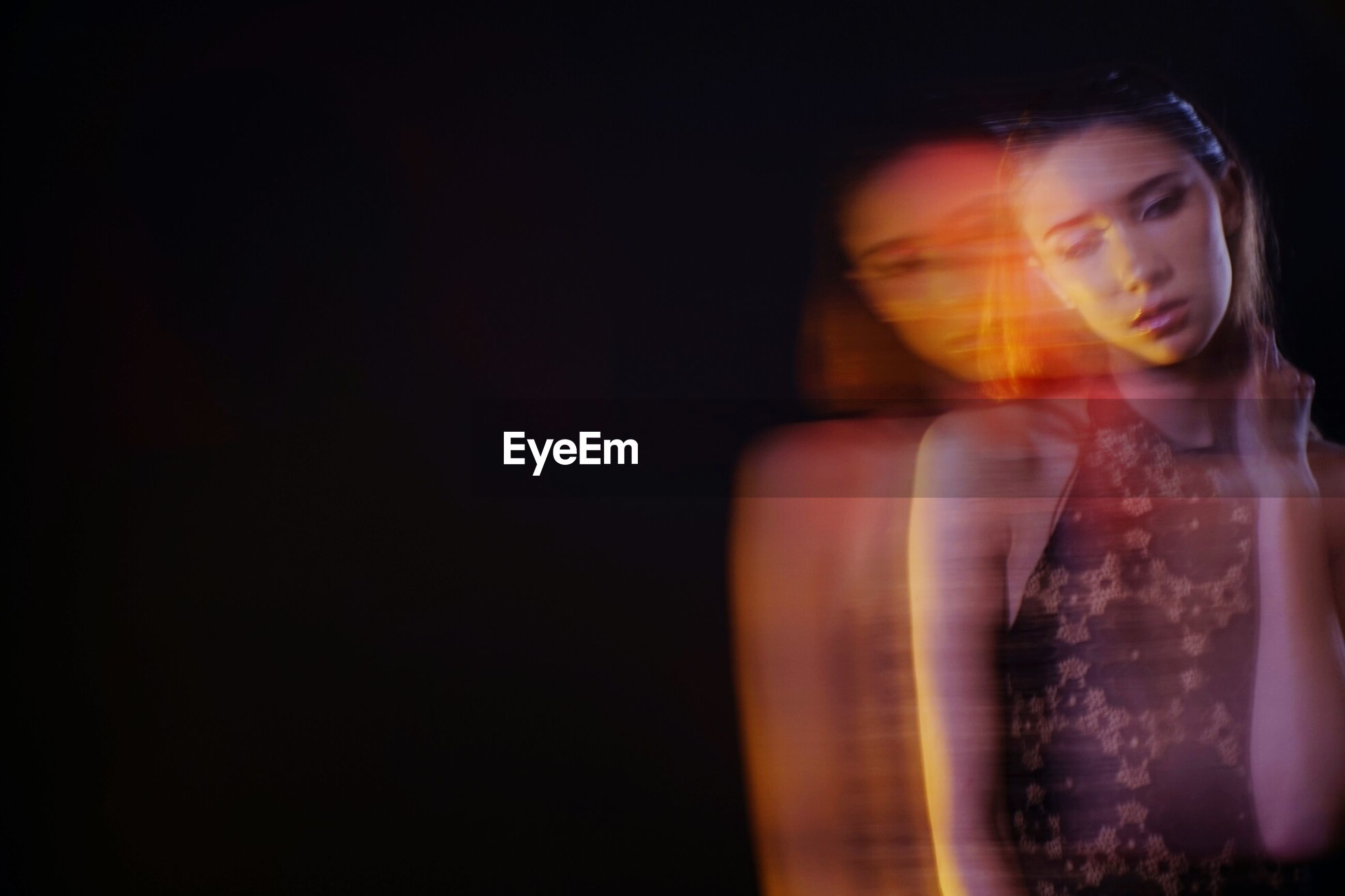 Blurred motion of thoughtful woman standing against black background