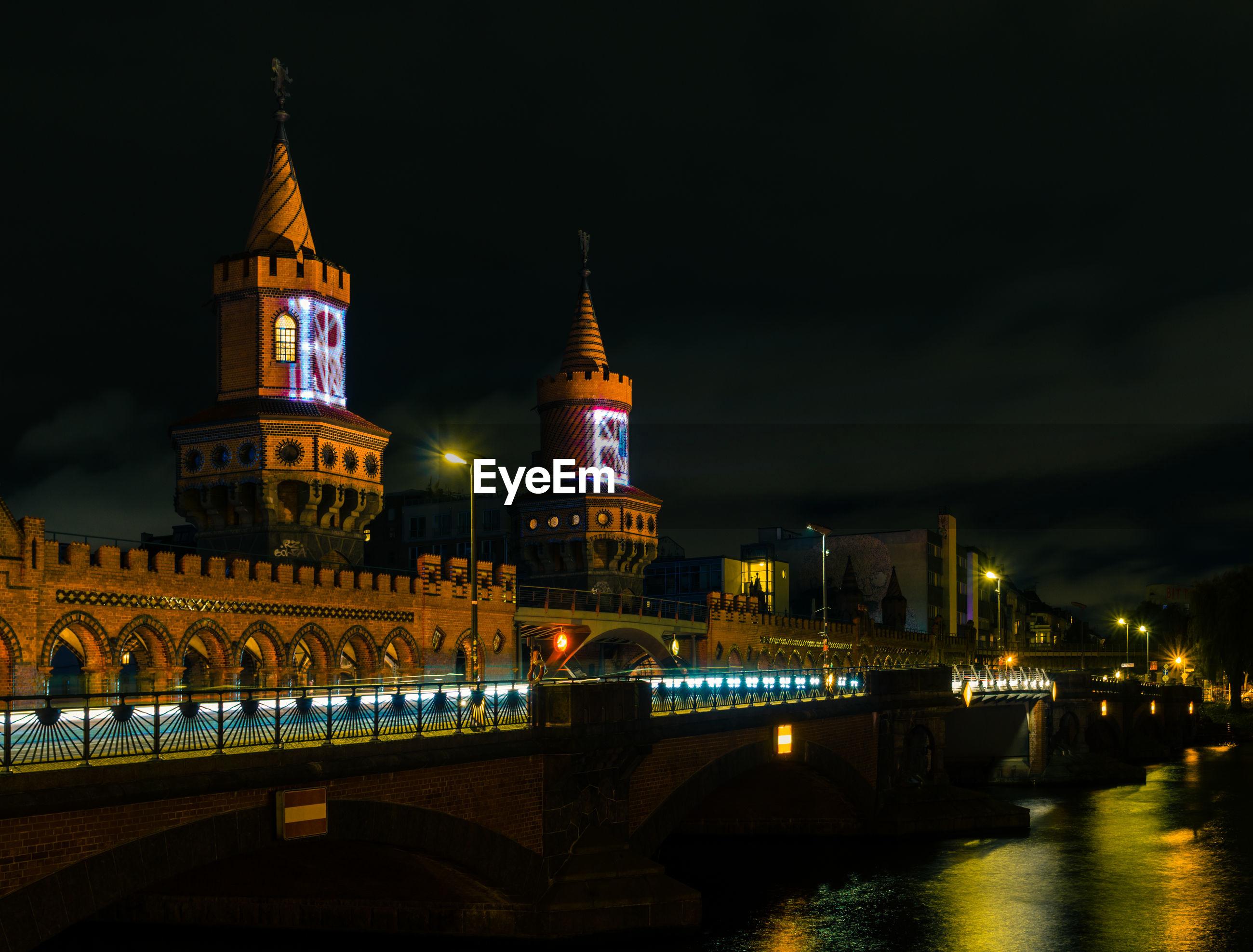 Oberbaum bridge over spree river against sky at night