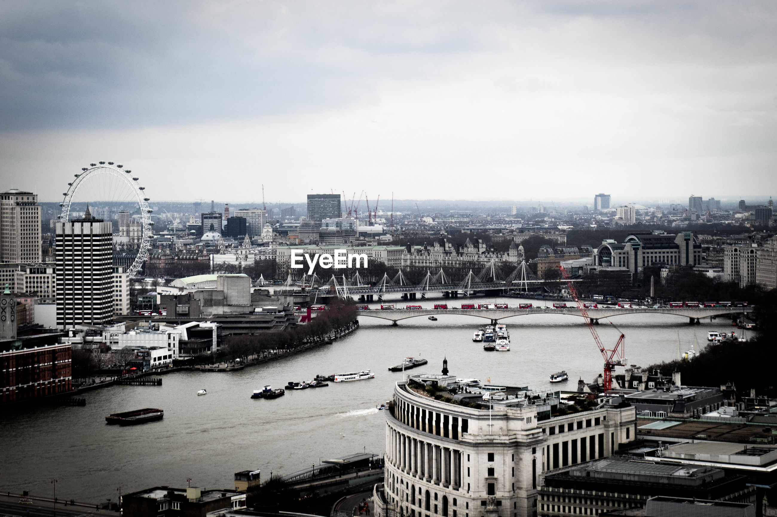 Thames river amidst cityscape against sky