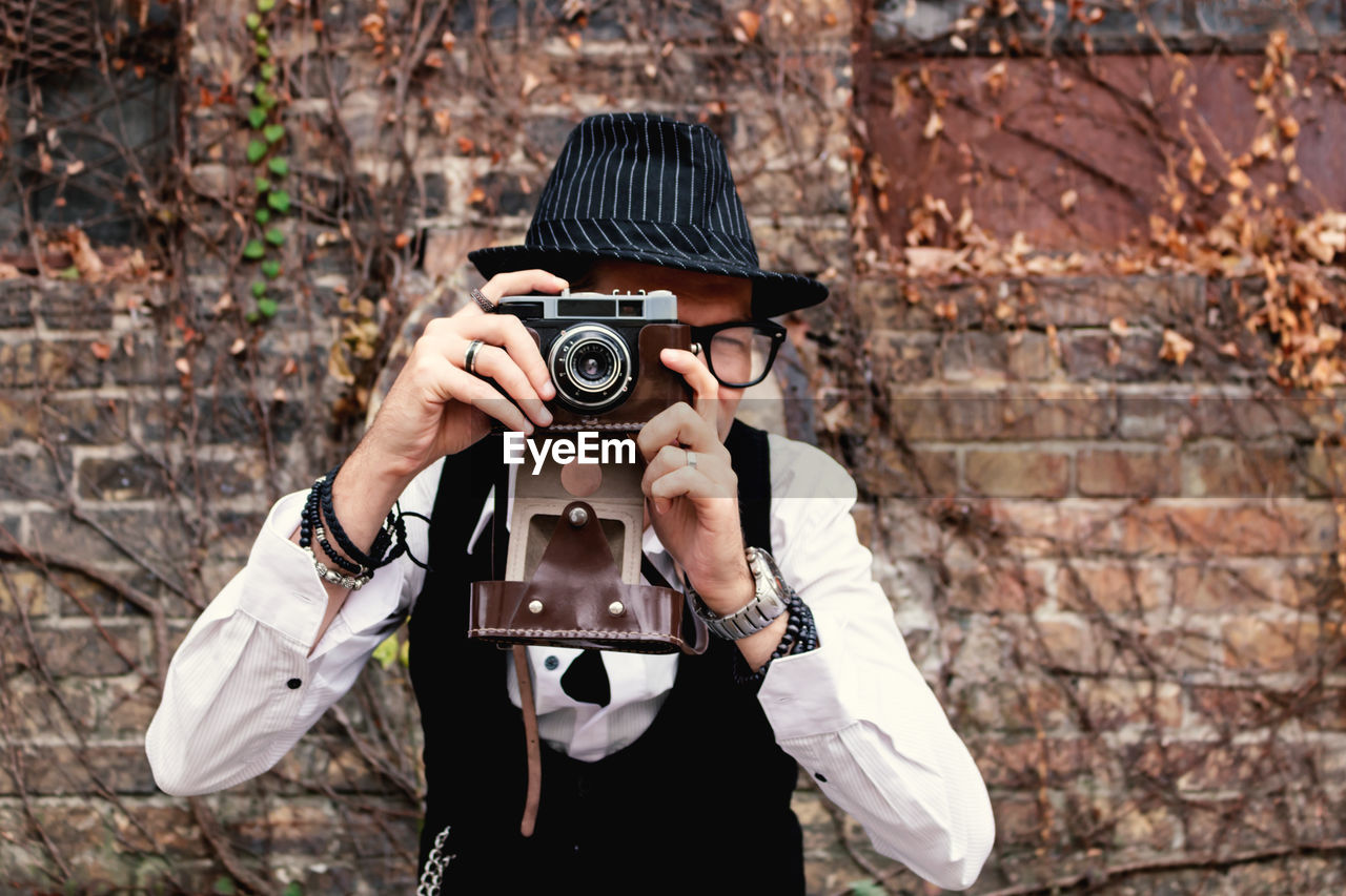 Retro-styled man photographing with analog photo camera outdoors.