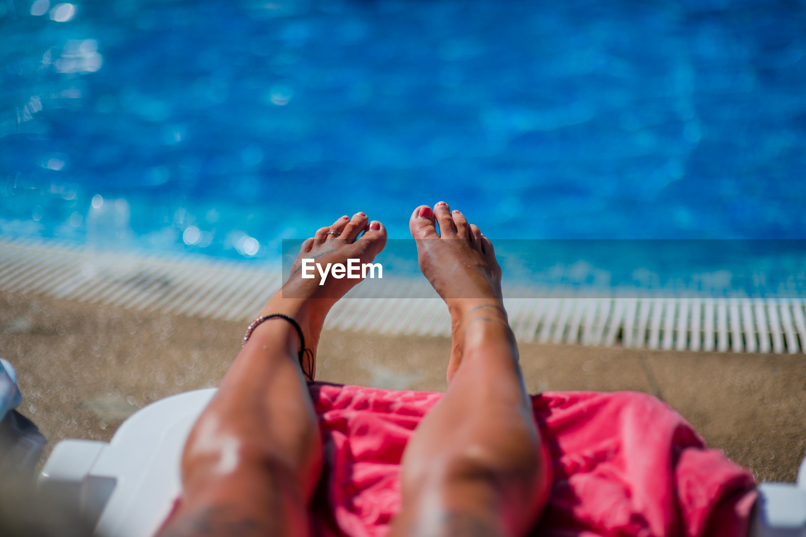 LOW SECTION OF WOMAN RELAXING BY SWIMMING POOL