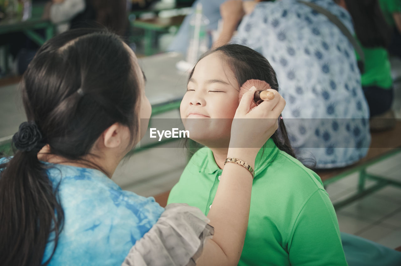 Mother Applying Make-Up Of Daughter With Brush