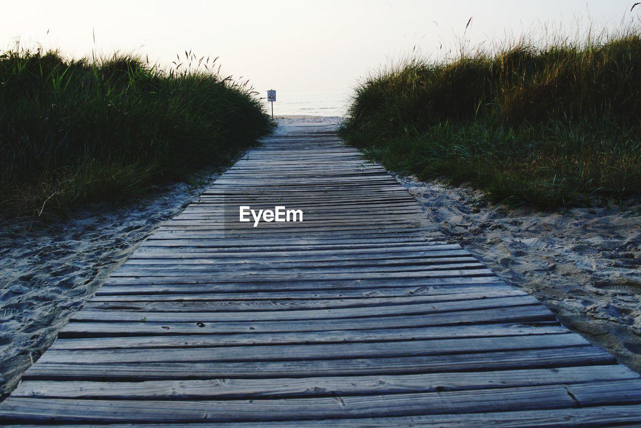 Walkway Leading Towards Beach Against Clear Sky