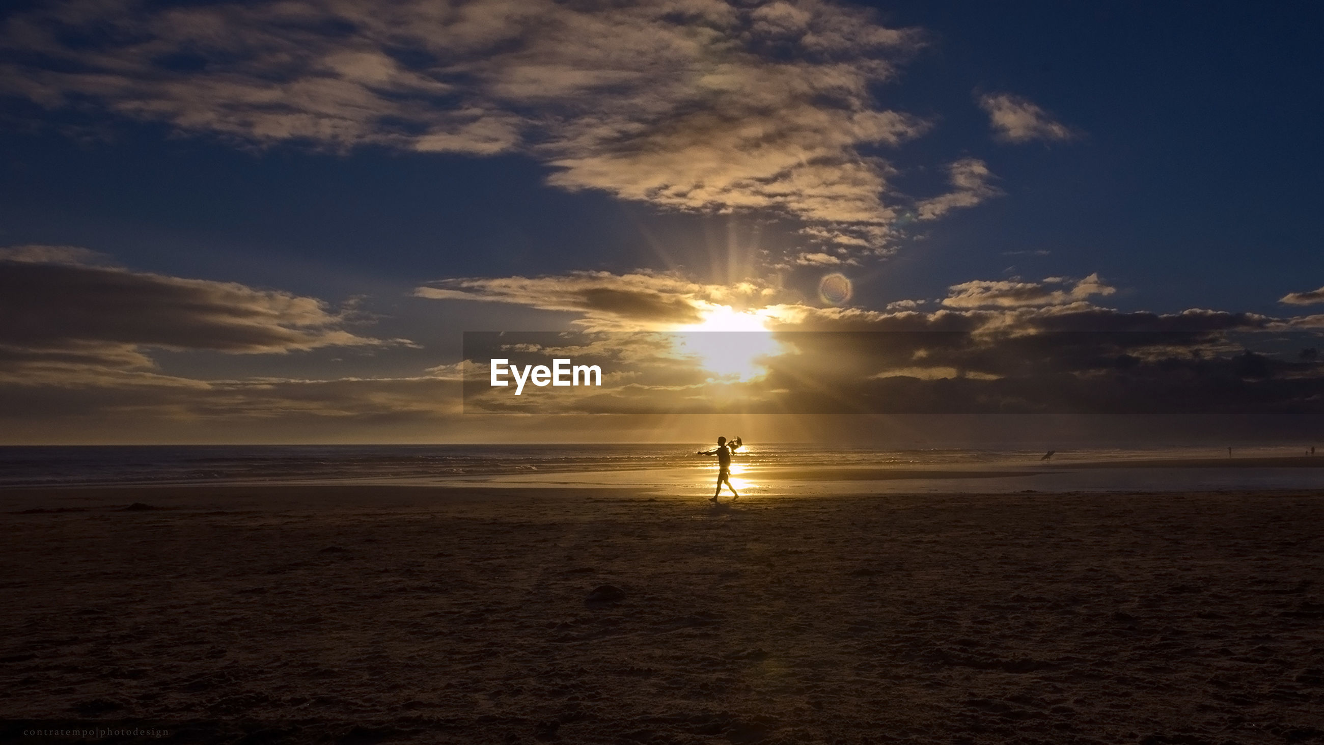Silhouette person walking on shore at beach against sky during sunset