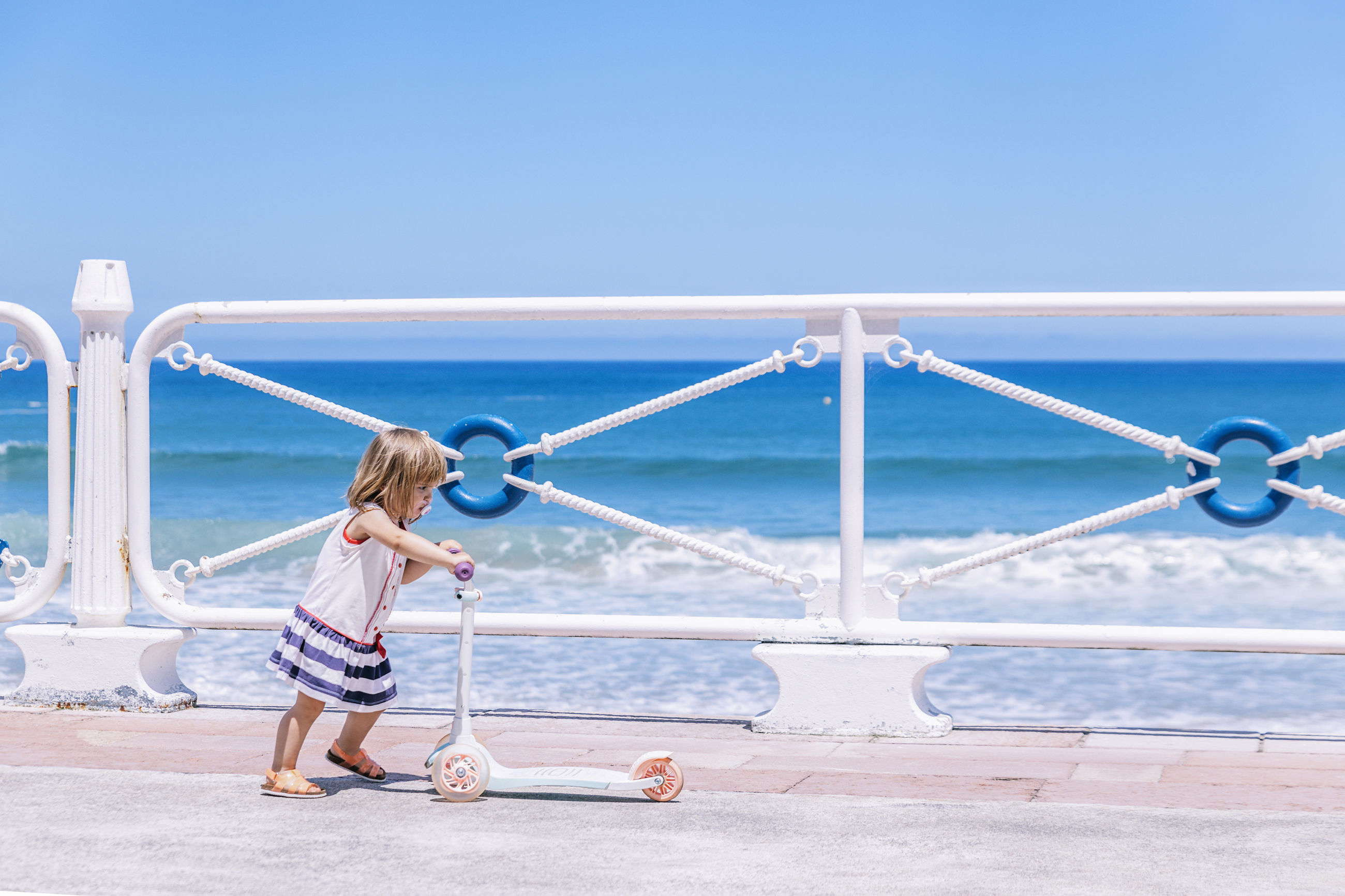 FULL LENGTH OF GIRL ON RAILING AGAINST SEA