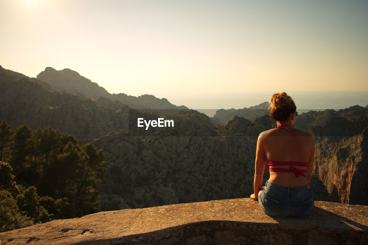 mountain, rear view, one person, scenics - nature, beauty in nature, leisure activity, lifestyles, sky, real people, tranquility, tranquil scene, looking at view, nature, non-urban scene, mountain range, vacations, trip, sitting, rock, rock - object, outdoors, hairstyle