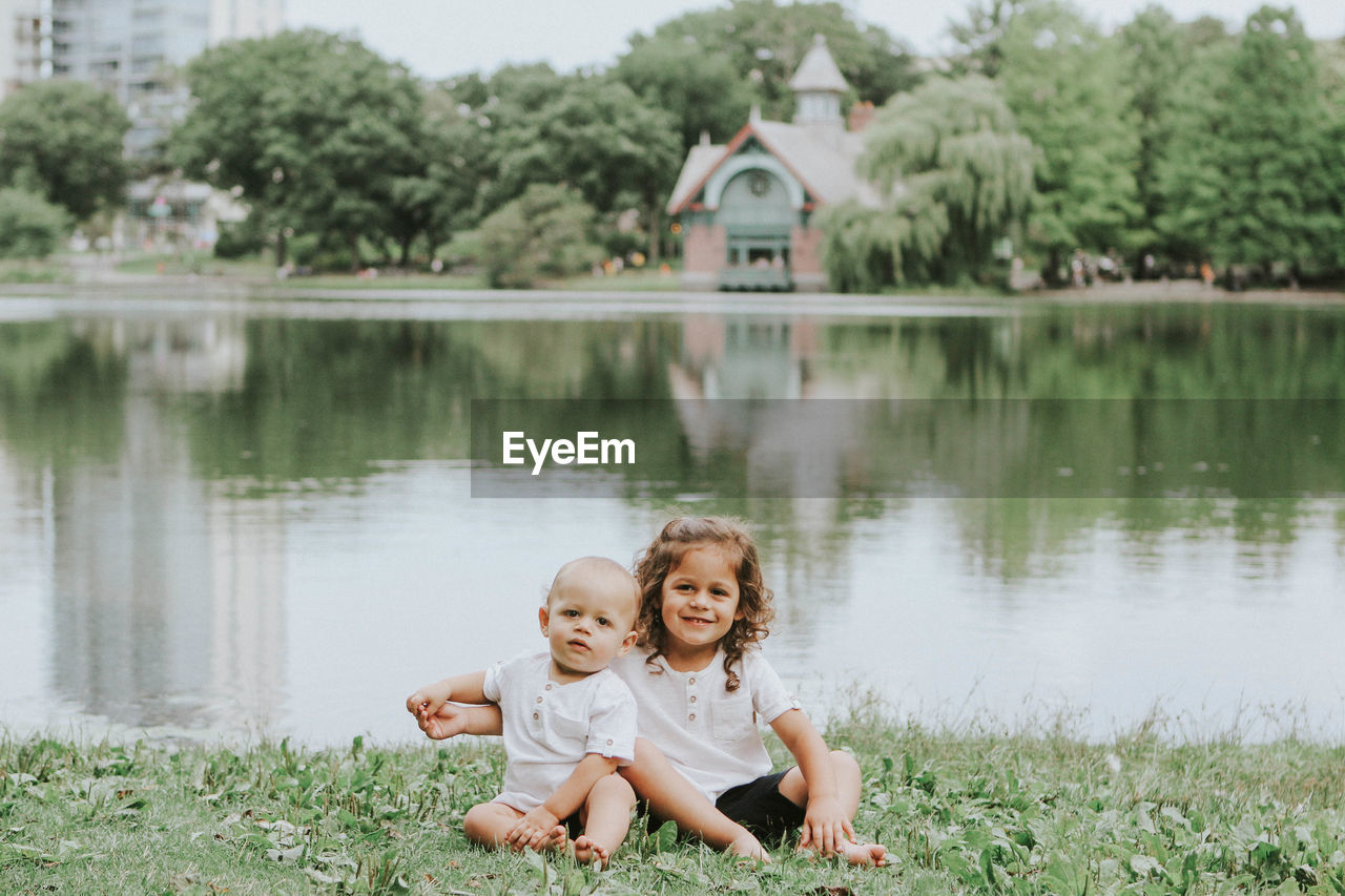 smiling, looking at camera, happiness, childhood, grass, togetherness, portrait, water, two people, day, building exterior, tree, girls, outdoors, full length, bonding, architecture, nature, people