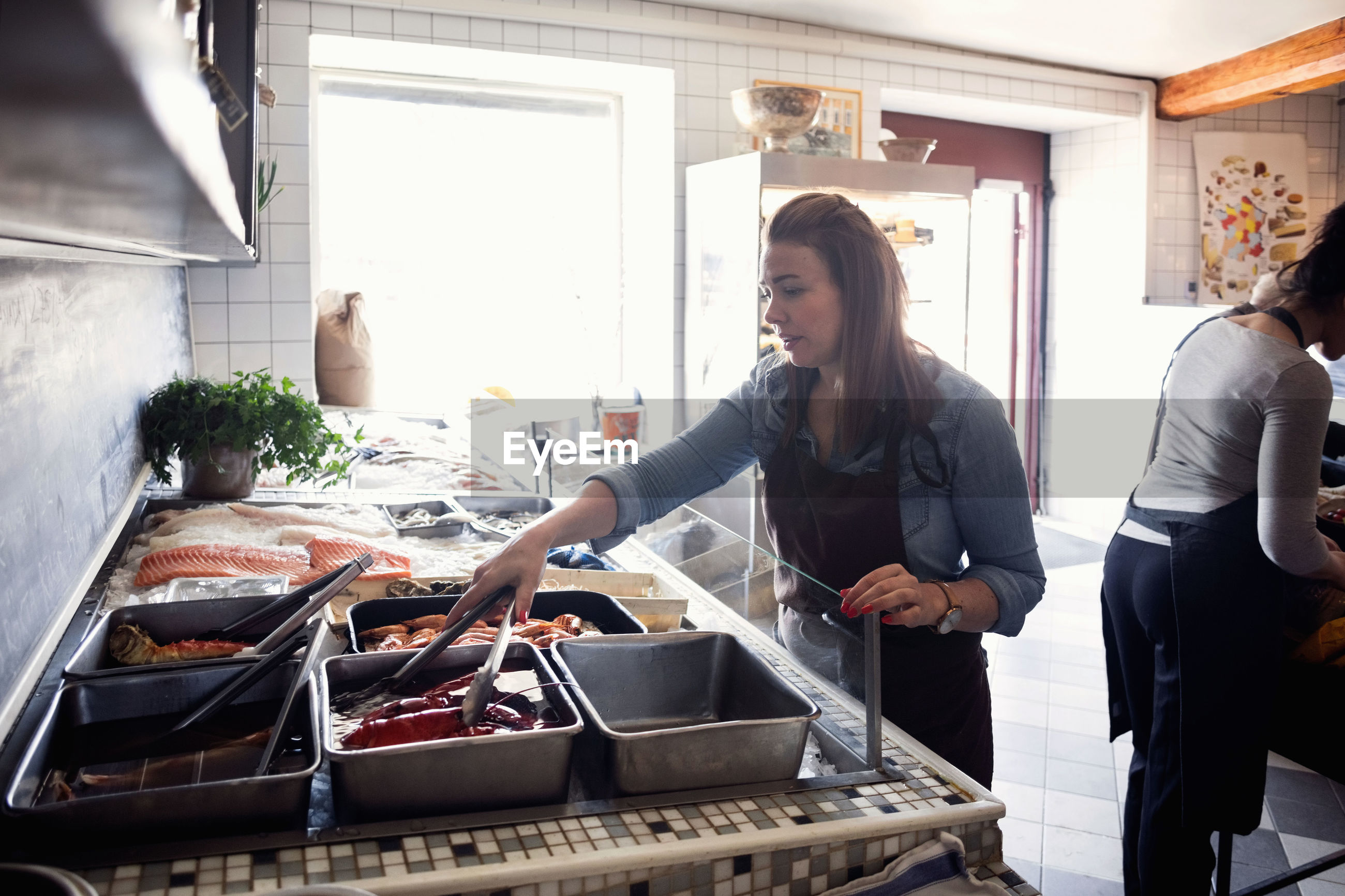 WOMAN STANDING BY FOOD IN A KITCHEN
