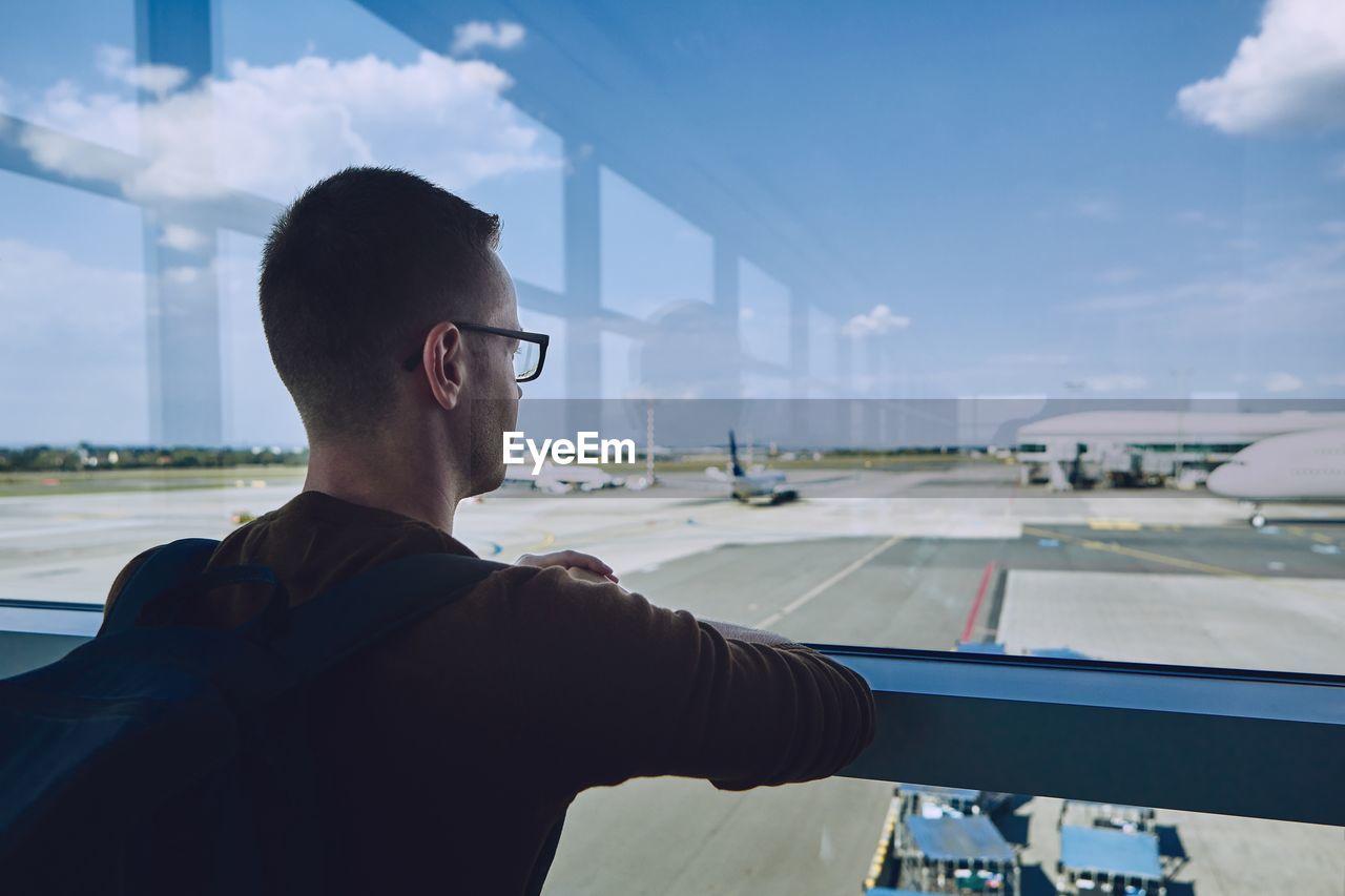 Man Looking At Airport Runway Through Window