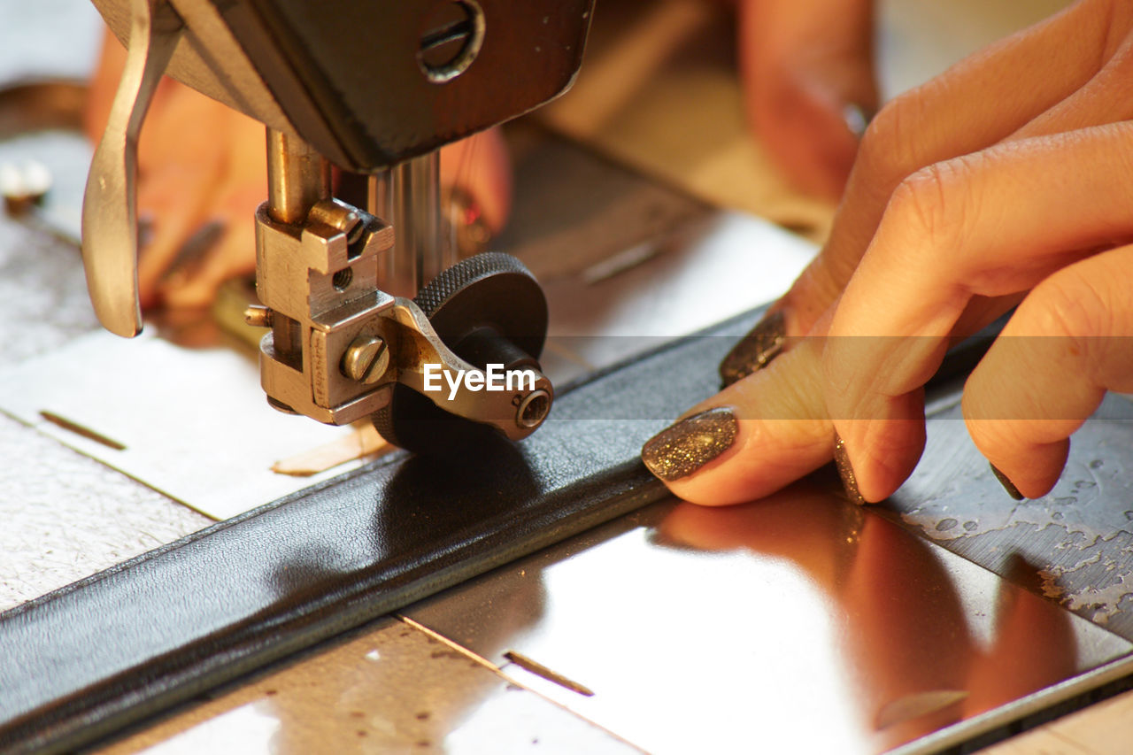 Cropped Hands Of Woman Using Sewing Machine