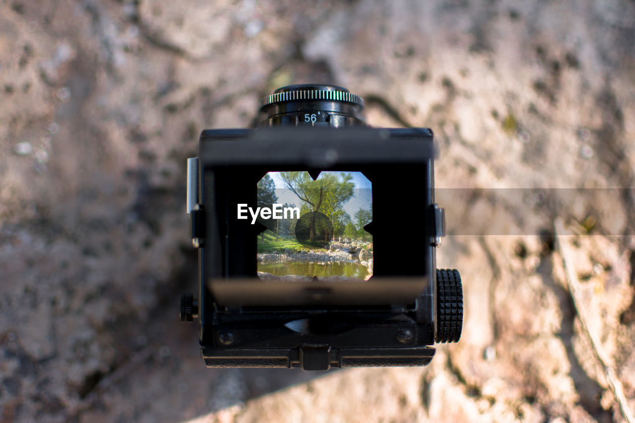 Close-up of vintage camera on rock