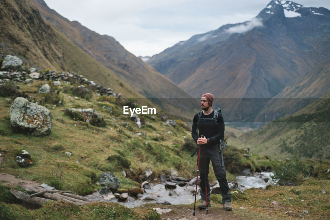Hiker Standing Against Mountains