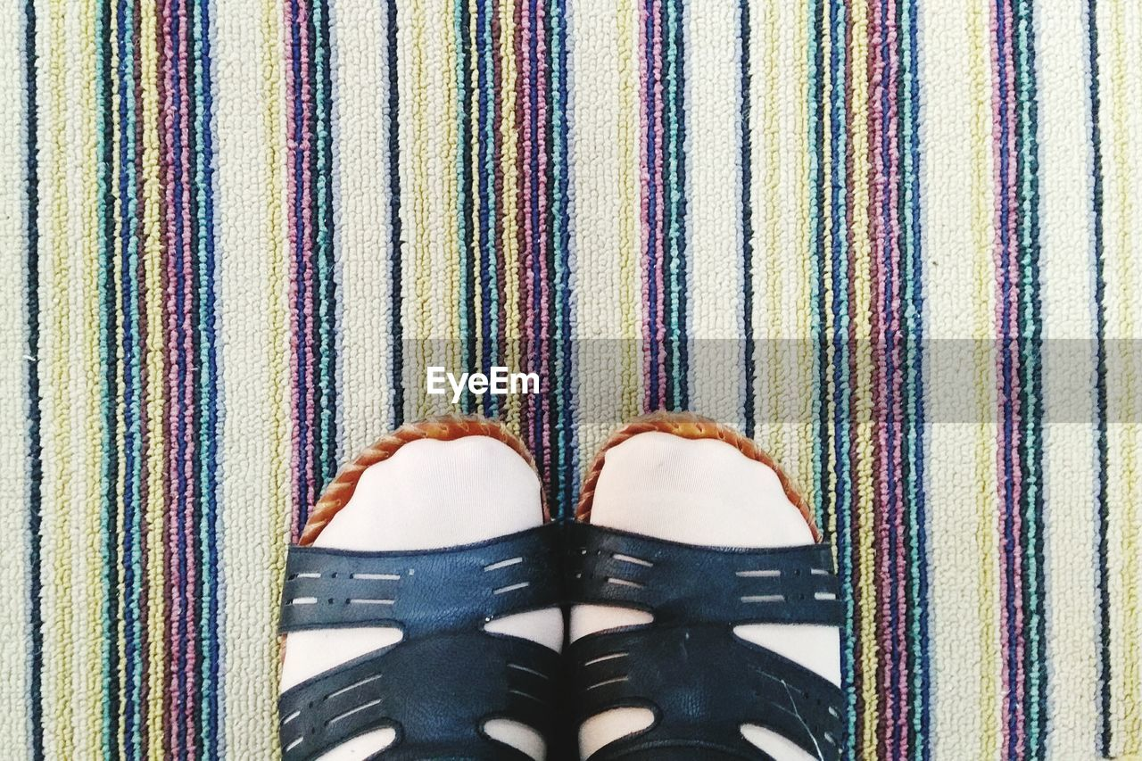 Low section of person wearing sandals while standing on carpet