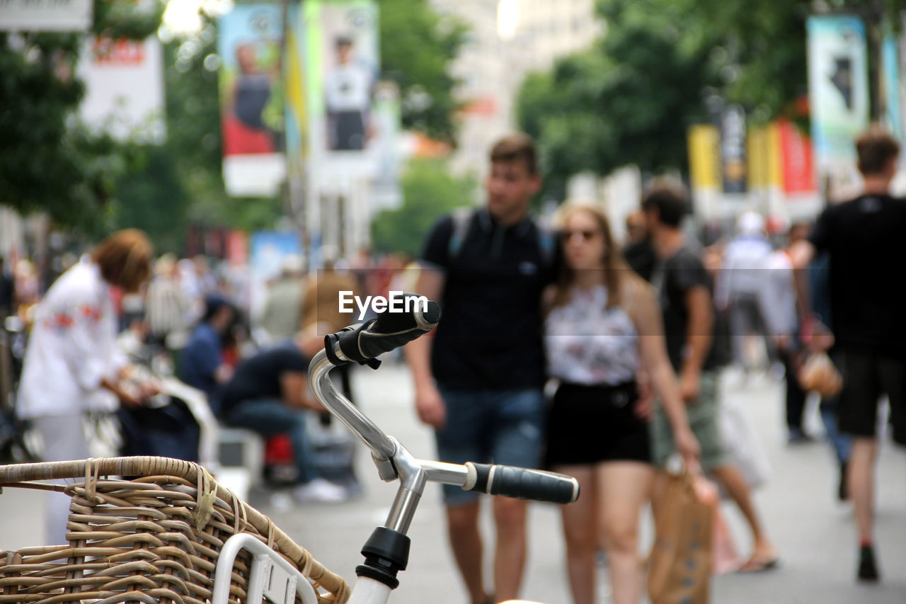 bicycle, transportation, focus on foreground, city, incidental people, street, group of people, real people, land vehicle, mode of transportation, women, lifestyles, men, day, adult, basket, people, casual clothing, outdoors, road