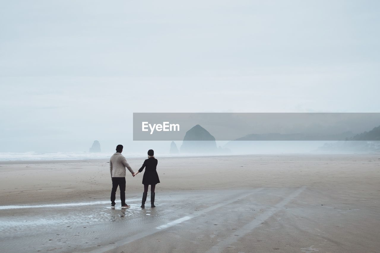 Rear View Of Couple Holding Hands While Standing At Beach During Foggy Weather