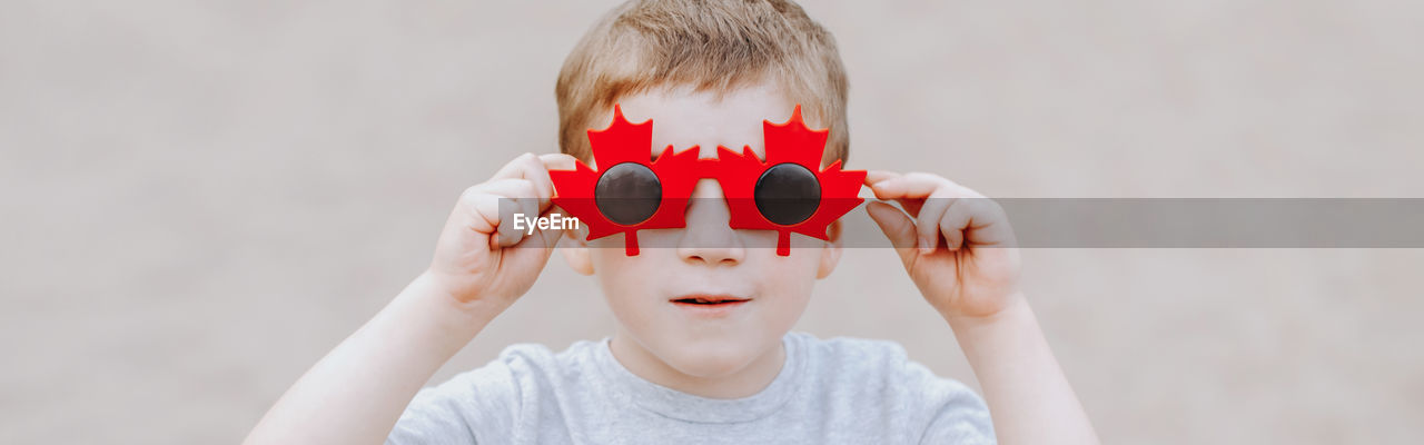 Boy wearing sunglasses against wall