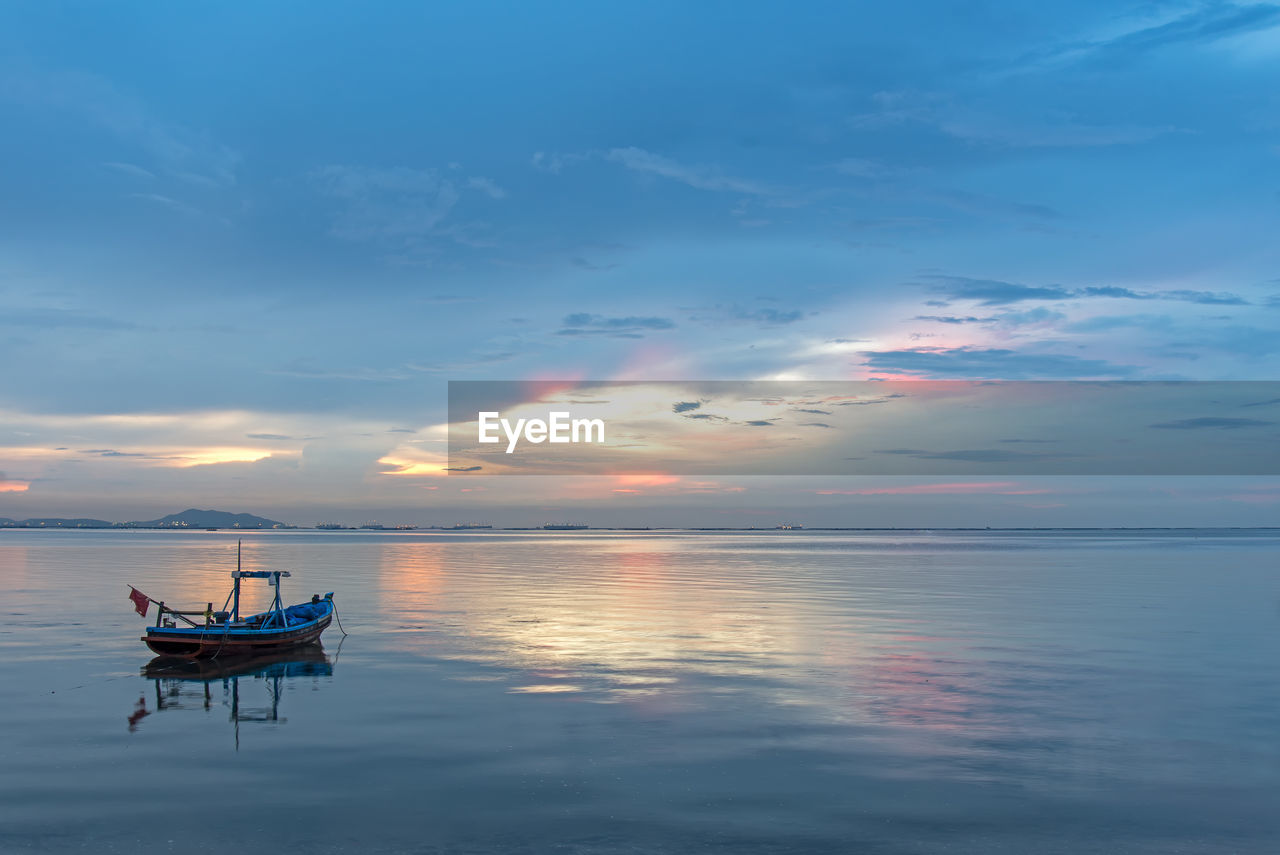 FISHING BOAT IN SEA DURING SUNSET
