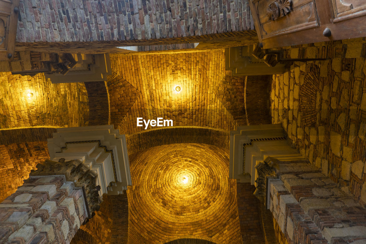 indoors, architecture, the past, no people, history, illuminated, built structure, lighting equipment, building, religion, travel destinations, low angle view, architectural column, ceiling, place of worship, gold colored, belief, spirituality, large group of objects, directly below