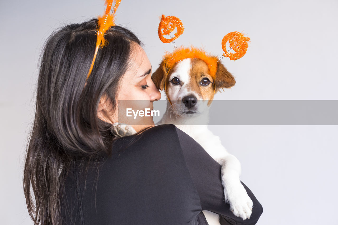 Rear view of woman with dog against white background
