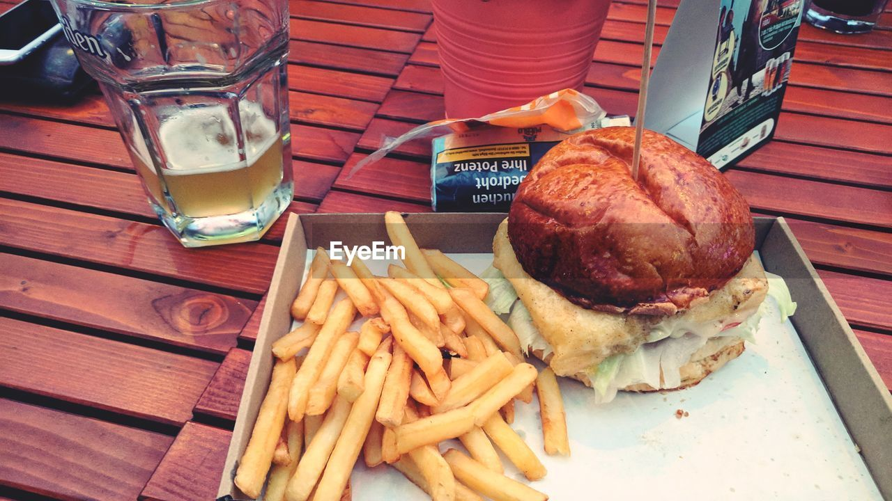 food and drink, food, prepared potato, french fries, table, unhealthy eating, drinking glass, freshness, burger, ready-to-eat, fast food, close-up, no people, indoors, hamburger, day