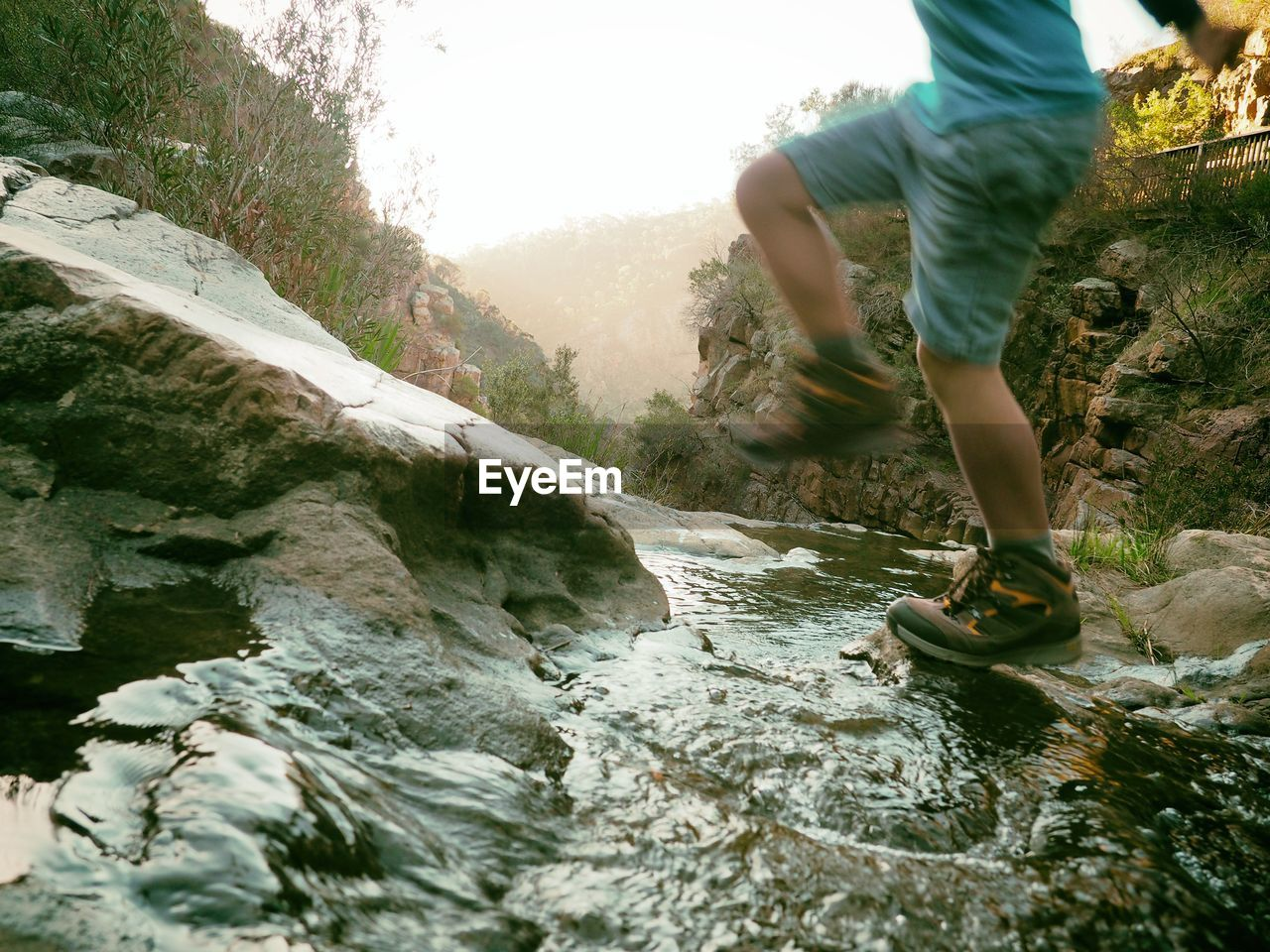 Low Section Of Boy Jumping On Rocks In River