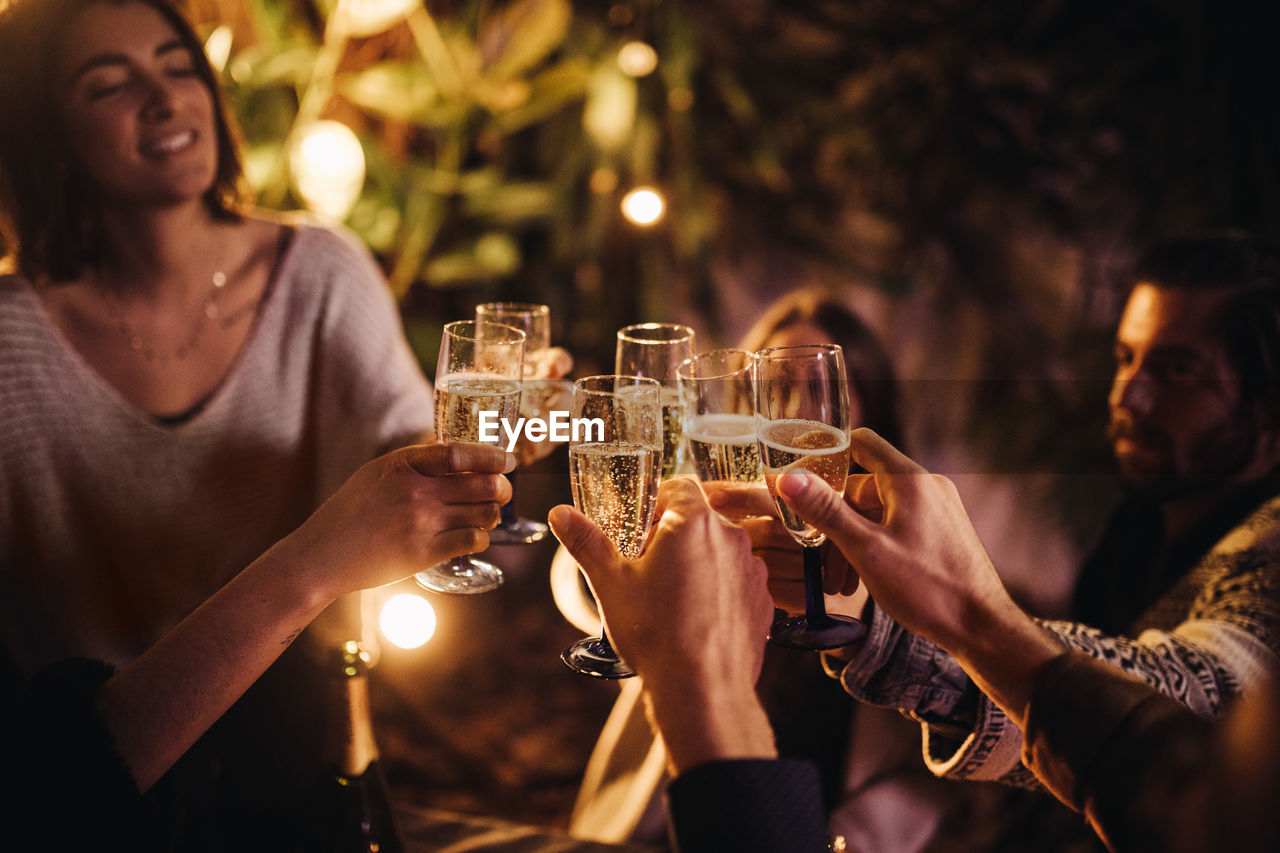 Cheerful friends toasting champagne during party