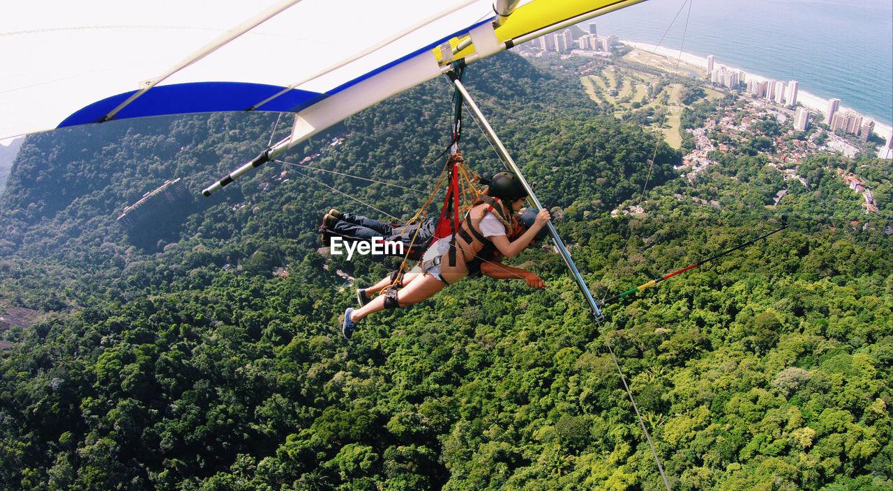 Man And Woman Hang Gliding Over Mountain