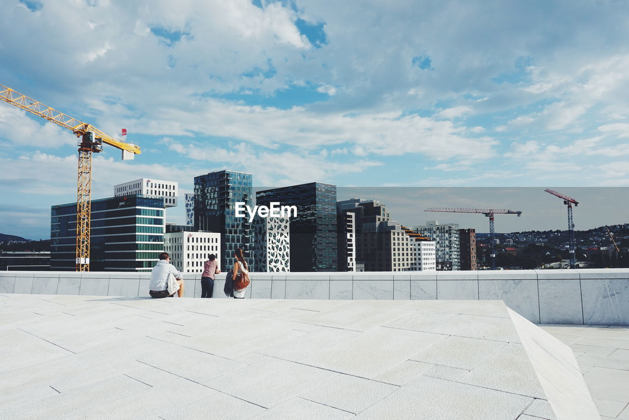 People On Oslo Opera House Against Sky In City