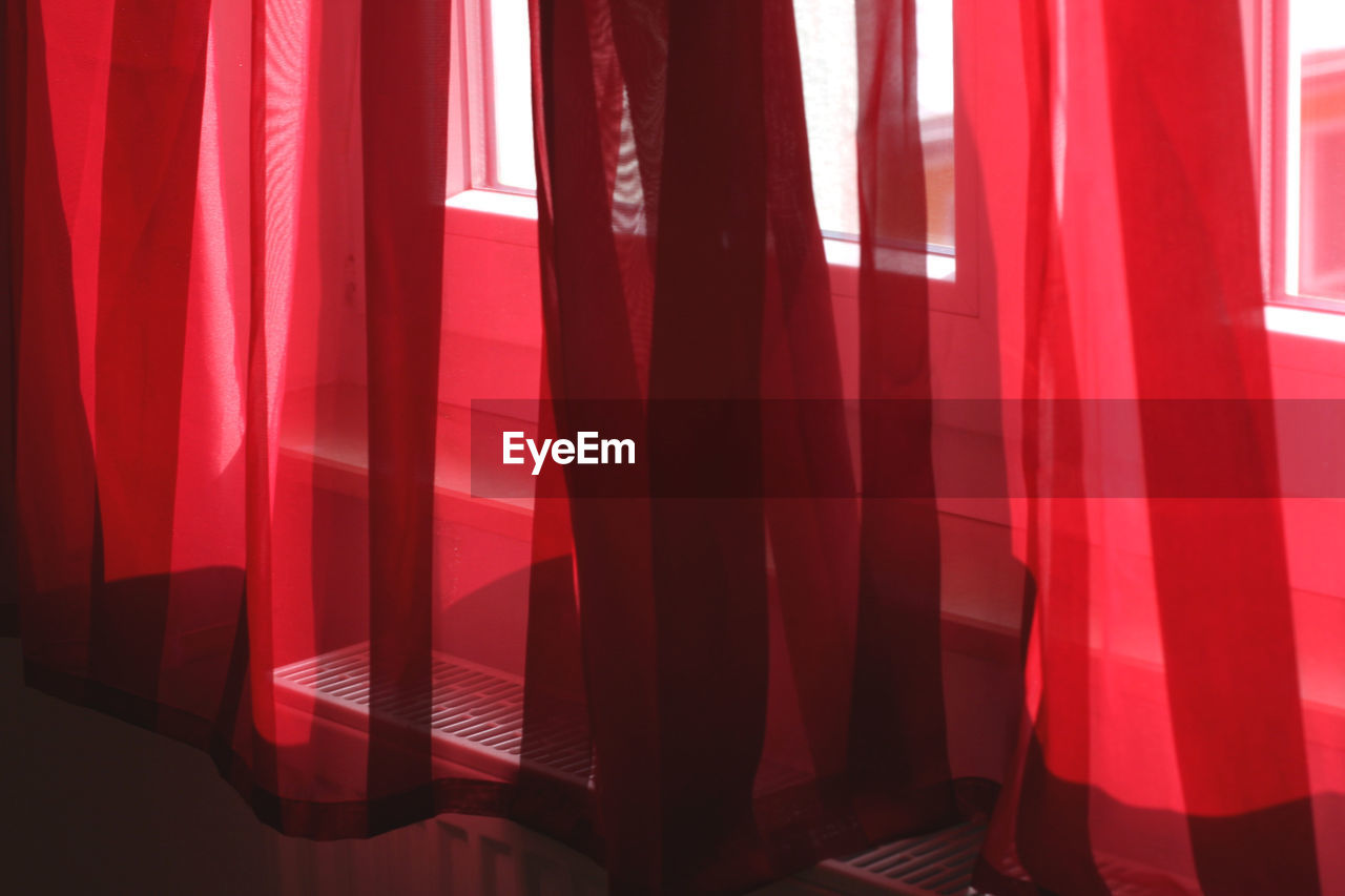 curtain, red, textile, indoors, no people, window, sunlight, shadow, home interior, hanging, day, absence, pattern, close-up, domestic room, seat, full frame, translucent, relaxation