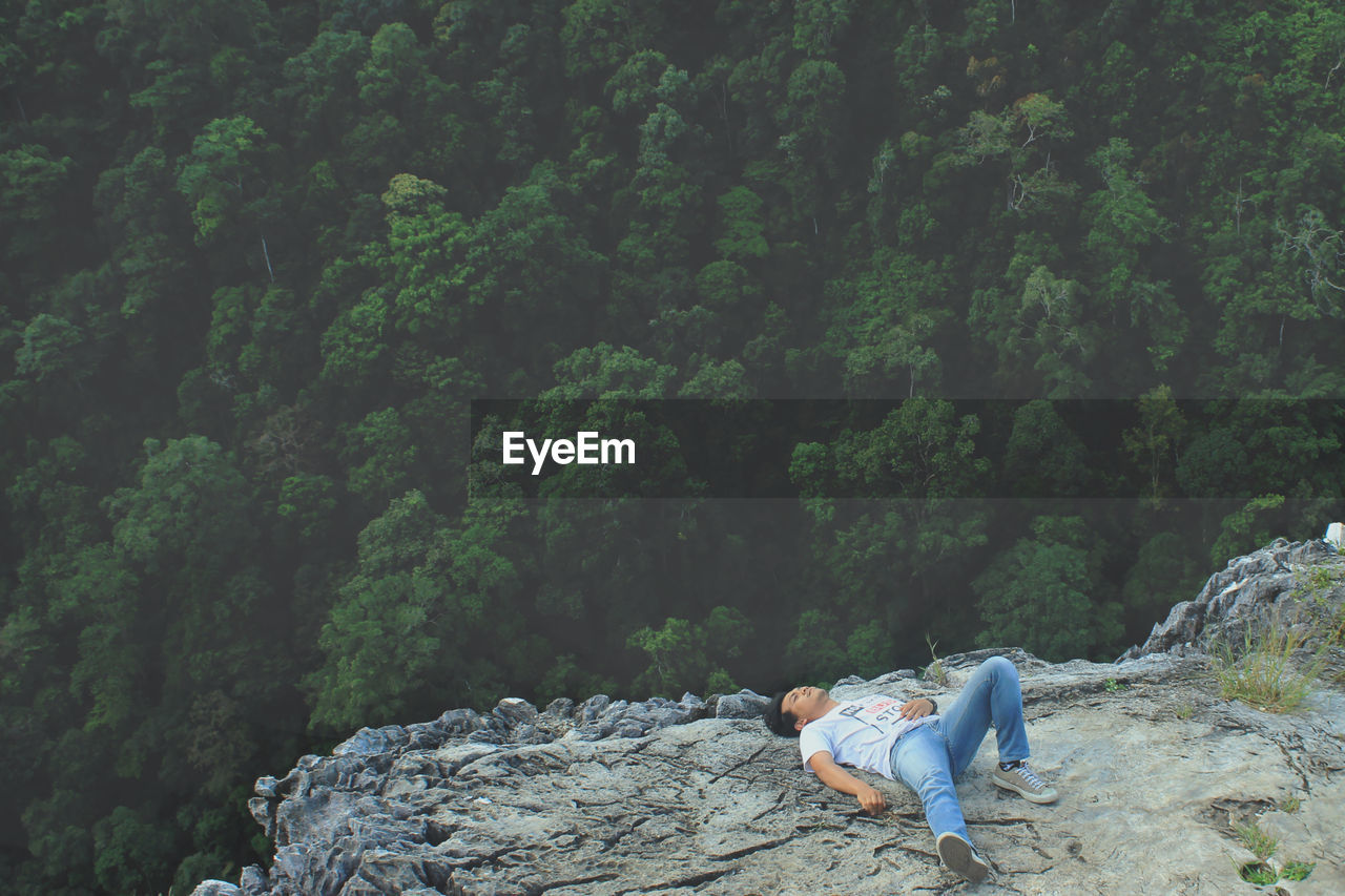 High Angle View Of Young Man Lying On Rocky Mountain Overlooking Dense Forest